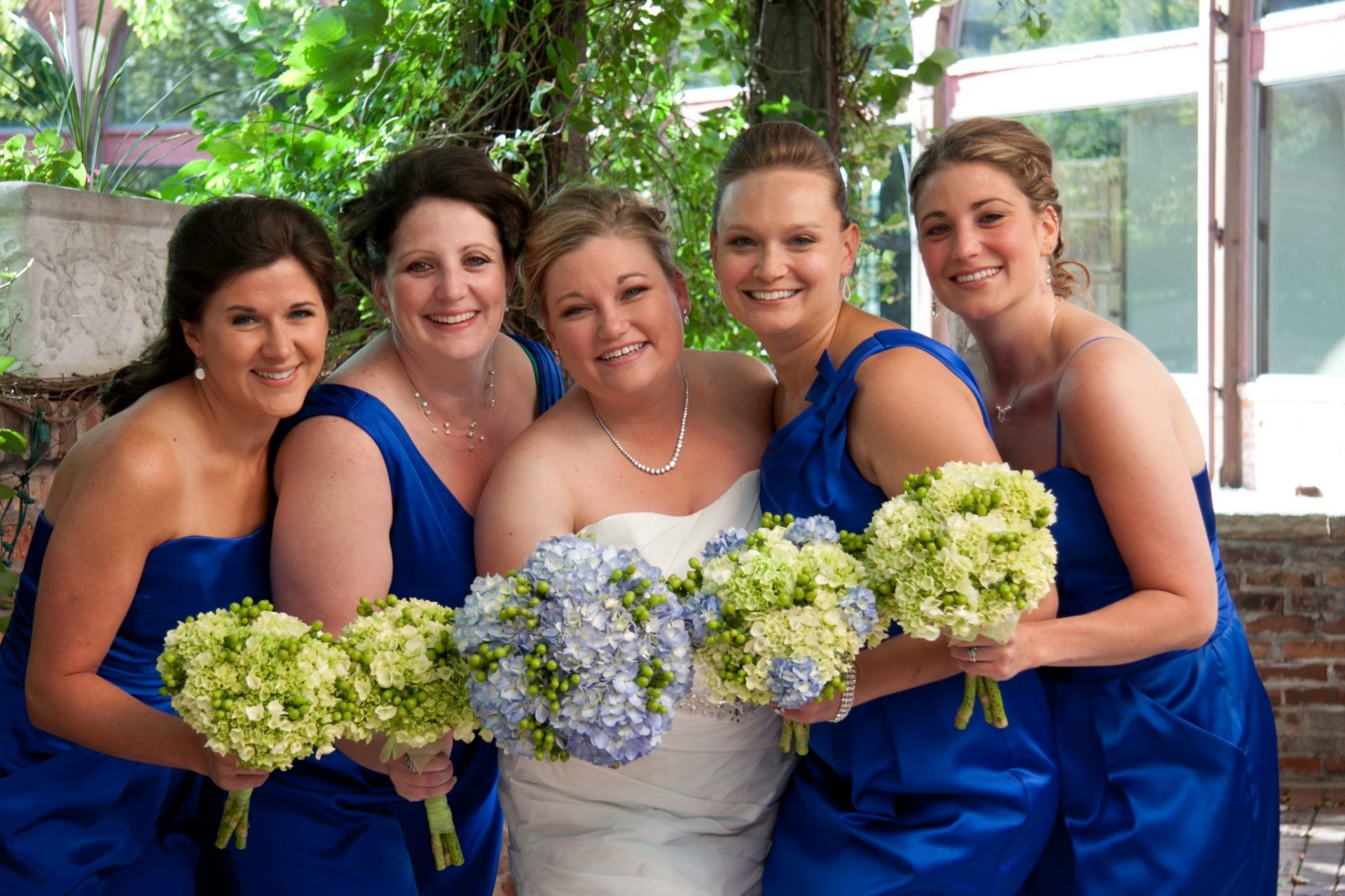 Blue and green wedding bouquets of hydrangea and hypericum berries.