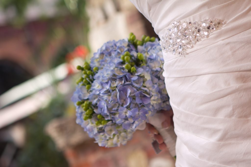 Brides bouquet of blue hydrangea with green hypericum.