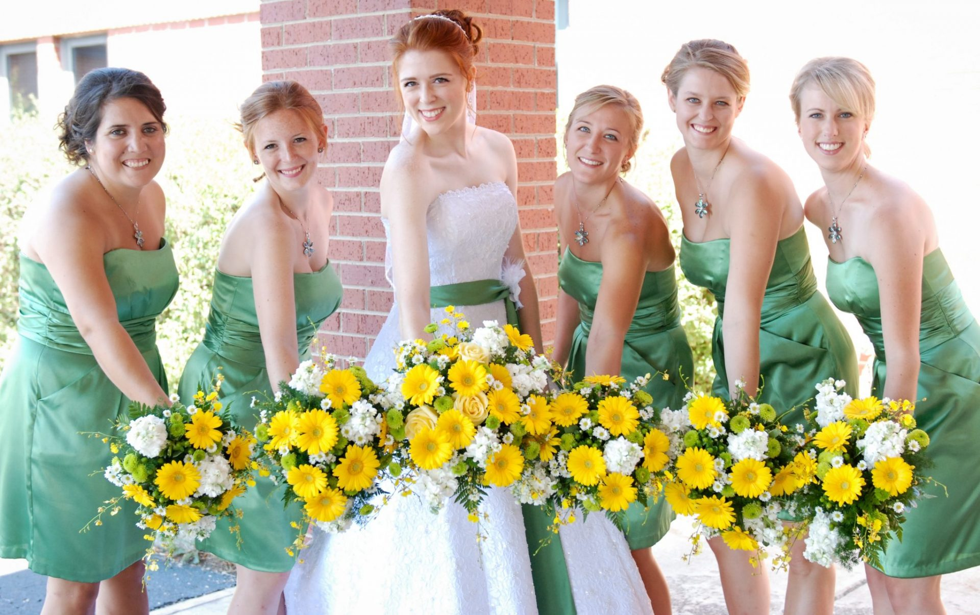 Yellow gerbera daisy bouquets with green and white accents.