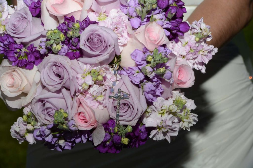 Bridal bouquet of pink and lavender roses with purple and lavender stock.