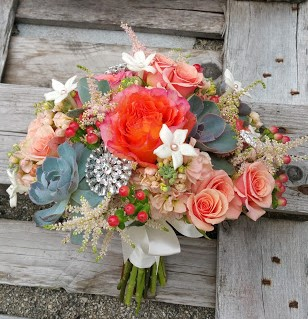 Peach roses, stephanotis, and succulents with sparkly accents for the bride.
