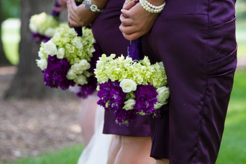 Lime green hydrangea make these bouquets pop against purple dresses. Purple stock and white roses complete the bouquets.