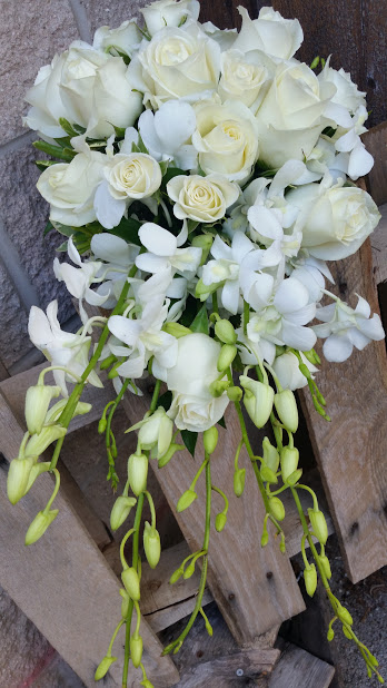 Cascading bridal bouquet of white roses and orchids.