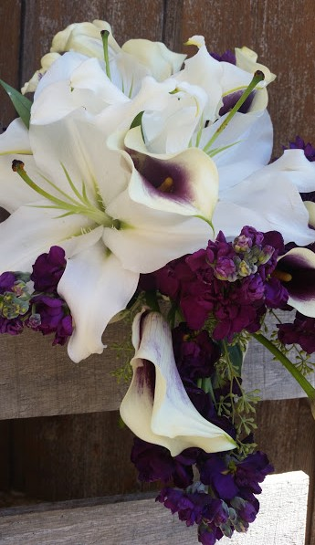 Purple and white bridal bouquet features oriental lilies, calla lilies and stock.