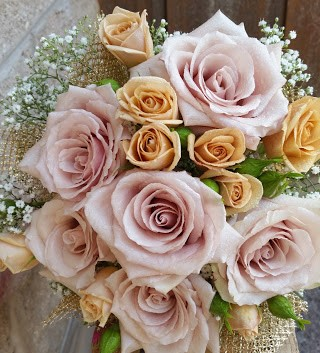 Dusty rose and champagne colored roses accented with babys breath and touches of gold in a romantic bridal bouquet.