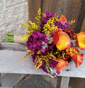 Calla lilies, roses, and stock in vibrant colors perfect for a fall wedding.