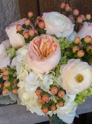 Peaches and cream color combination - hydrangea, ranunculus, garden roses, and hypericum berries.
