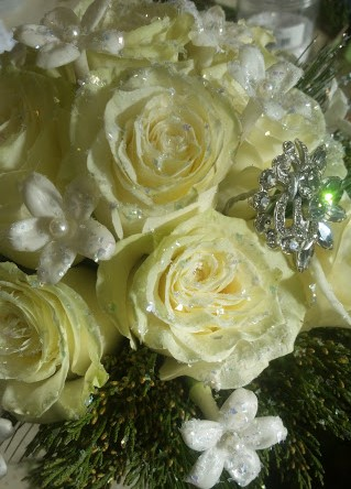 Glittered, bejeweled, and festive, this bridal bouquet features white roses, stephanotis.