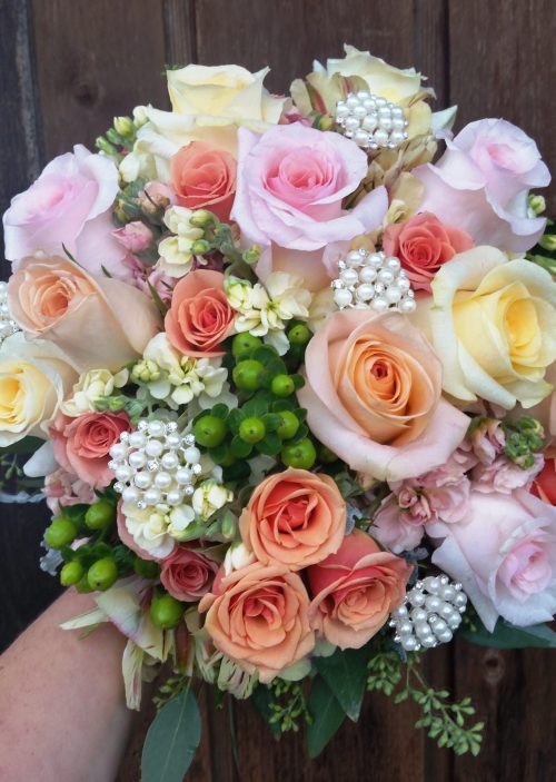 A romantic bouquet of roses in a blend of pastel colors is adorned with clusters of pearls.
