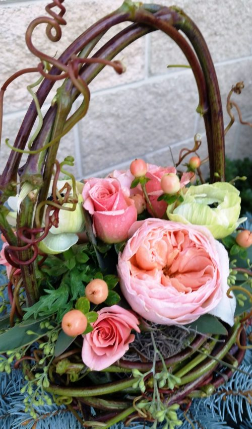 A sweet flower girl basket created with fresh grapevine and filled with roses and ranunculus.