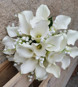 Elegant white calla lilies adorned with delicate lily of the valley.