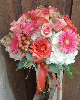 Peach and pink bouquet of hydrangea, roses, gerbera daisies, hypericum and seeded eucalyptus.