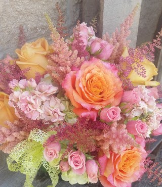 Free Spirit roses are the focal flower in this pretty peach & pink bouquet.