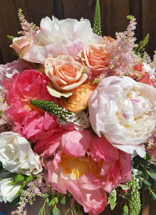 Bridal bouquet of peonies in white, pink and peach with accents of roses, veronica, and astilbe.