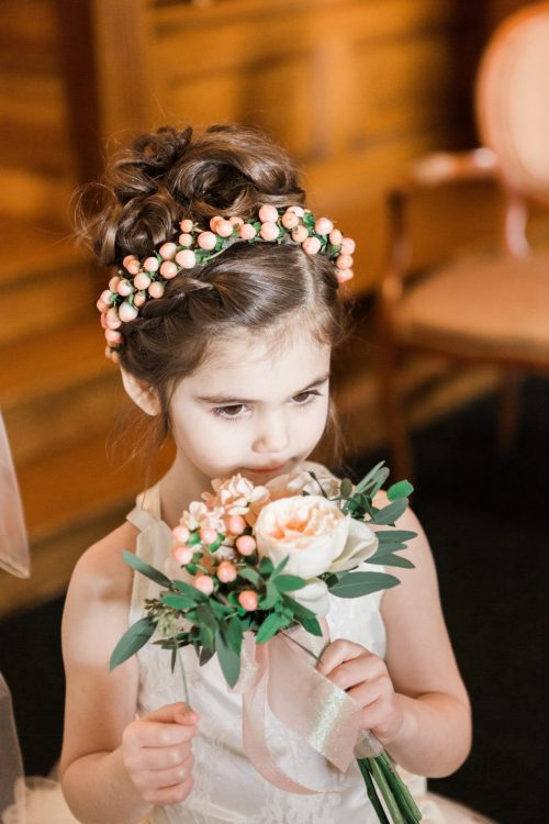 Miniature clutch bouquet of peach garden roses, stock, and hypericum for the flower girl with matching crown of hypericum berries.